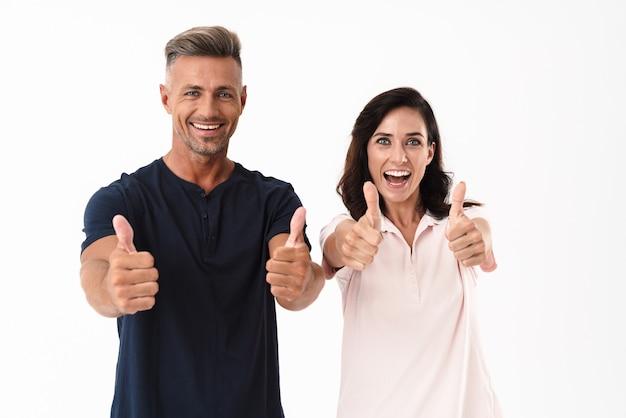 Веселая привлекательная пара в повседневной одежде стоит изолированно над белой стеной и показывает палец вверх