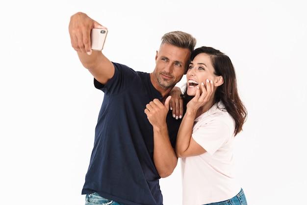 白い壁の上に孤立して立っているカジュアルな服を着て、自分撮りをしている陽気な魅力的なカップル