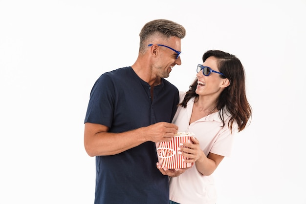 Cheerful attractive couple wearing casual outfit standing isolated over white wall, watching a movie with popcorn and 3d glasses