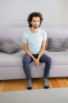 カジュアルなtシャツを着て、自宅のソファに座って、目をそらして笑っている陽気な魅力的な縮れ毛の若い男。垂直ショット。男性の肖像画の概念