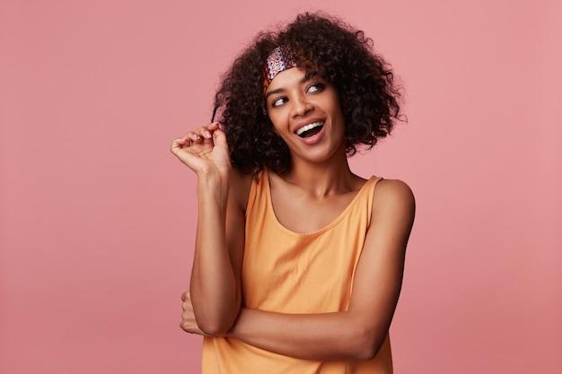 Allegra attraente signora bruna dalla pelle scura con acconciatura casual che gioca con i suoi capelli ricci mentre guarda sognante da parte, indossando abiti casual e fascia colorata