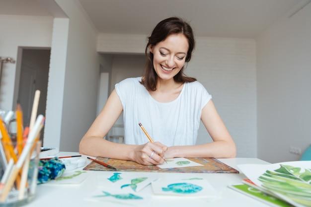 Веселая привлекательная женщина-художник делает эскизы за столом в мастерской