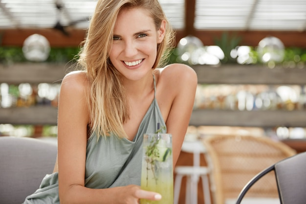 Cheerful attractive female with positive expression enjoys leisure time at cafeteria, drink cold fresh cocktail, spends summer vacation in resort country.