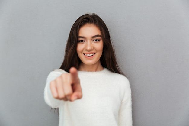 Веселая привлекательная девушка в белом пушистом пуловере, указывая пальцем на тебя