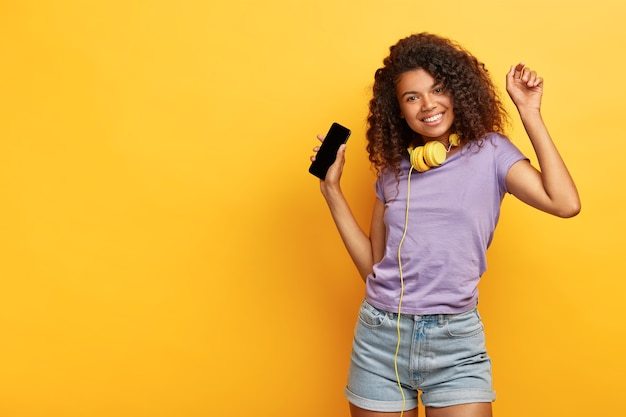 곱슬 머리, 어두운 피부를 가진 쾌활한 매력적인 소녀는 온라인 웹 사이트에서 다운로드 한 멋진 노래를 즐기고 헤드폰을 착용합니다.