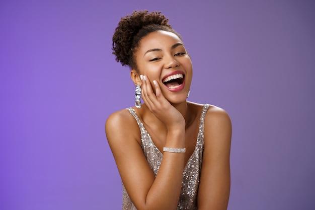 우아한 은색 드레스를 입은 쾌활하고 매력적인 행복한 아프리카계 미국인 여성은 남자친구 감각 유머 농담을 즐기며 낄낄거리며 웃으면서 뺨에 요염한 시선을 즐겁게 하고 파란색 배경을 만집니다.