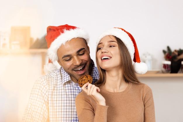 Веселая привлекательная счастливая пара в шляпах санта-клауса