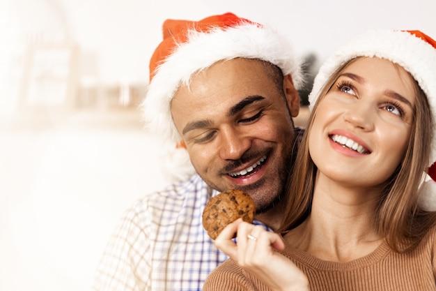 サンタの帽子で陽気な魅力的な幸せなカップル