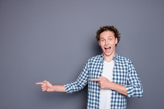 2本の指を脇に向けるカジュアルな市松模様のシャツを着た陽気な魅力的な男