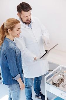 쾌활한 매력적인 좋은 여자가 그녀의 의사 근처에 서서 그녀의 성형 수술에 대해 종료되는 동안 태블릿 화면을보고