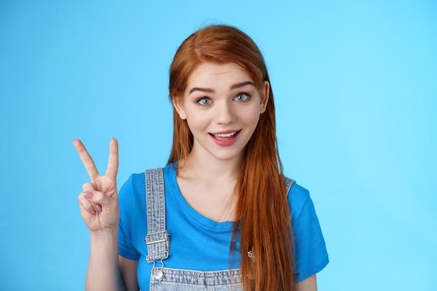 쾌활하고 매력적인 빨간 머리 백인 소녀는 즐겁게 말하고, 두 개의 평화를 주문하고, 두 번째 번호를 보여주고, 평화 승리 기호를 보여주고, 평온하고, 낙관적인 감정을 갖고, 파란색 배경을 서 있습니다.