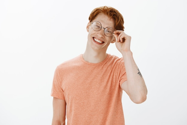 Cheerful attractive redhead man smiling and looking carefree, wearing glasses