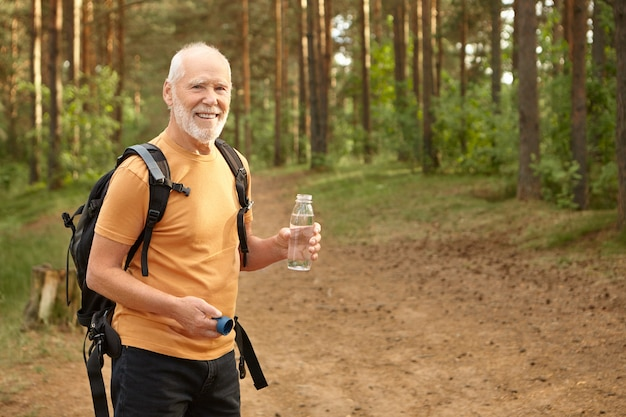 Cheerful attractive senior man with backpack hiking outdoors, smiling joyfully satisfying his thirst, holding bottle with drinking water, posing in pine forest. age, maturity and active lifestyle