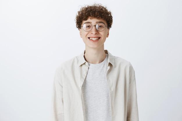Веселый привлекательный парень-подросток позирует у белой стены