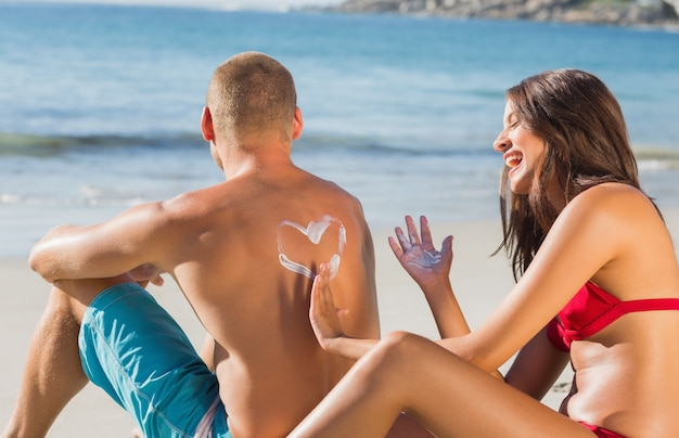Cheerful attractive woman applying sun cream on her boyfriends back