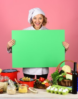 陽気な魅力的な女性シェフは、野菜の束が緑のボードを保持しているテーブルに立っています