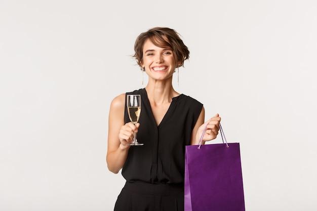 샴페인 잔을 마시고 선물 가방을 들고 쾌활한 매력적인 여자는 흰색 위에 서있는 생일 파티에 참석합니다.
