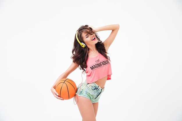 Cheerful attractive woman holding basketball ball and listening music in headphones isolated