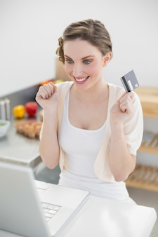 Cheerful attractive woman homeshopping with her notebook