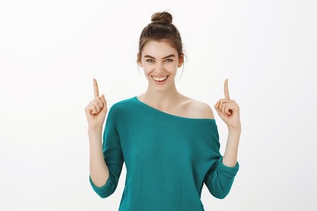 イベントに招待し、広告に指を向けて陽気な魅力的な女性