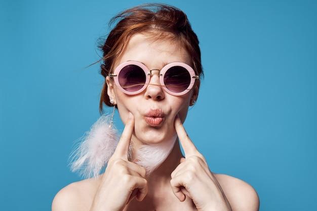 쾌활 한 매력적인 여자 벌 거 벗은 어깨 귀걸이 보석 감정 자른보기 파란색 배경. 고품질 사진