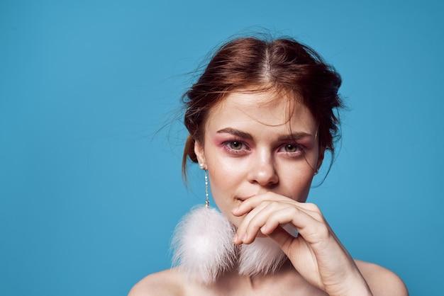 Веселая привлекательная женщина обнаженные плечи серьги ювелирные изделия эмоции обрезанный вид синий фон.