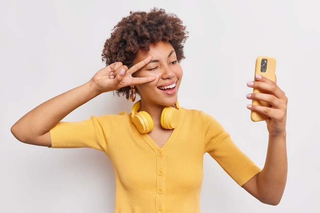Cheerful attractive woman with afro hair makes sefie records video on smartphone makes peace gesture over eye stands happy uses modern technologies for entertainment isolated on white studio wall