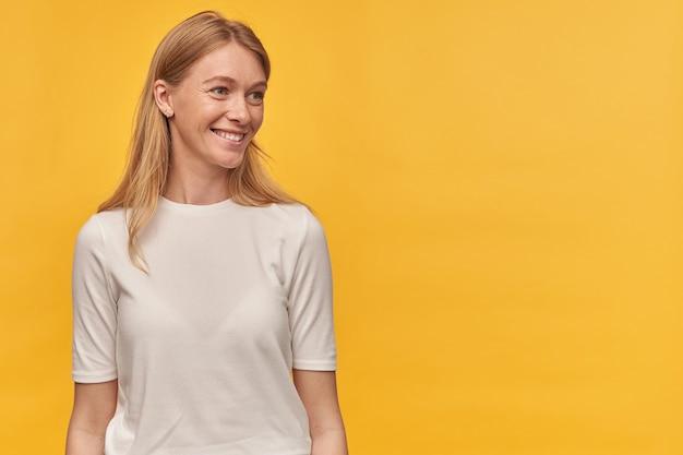 笑顔と黄色の空きスペースで横に目をそらしている白いtシャツのそばかすのある陽気な魅力的な女性