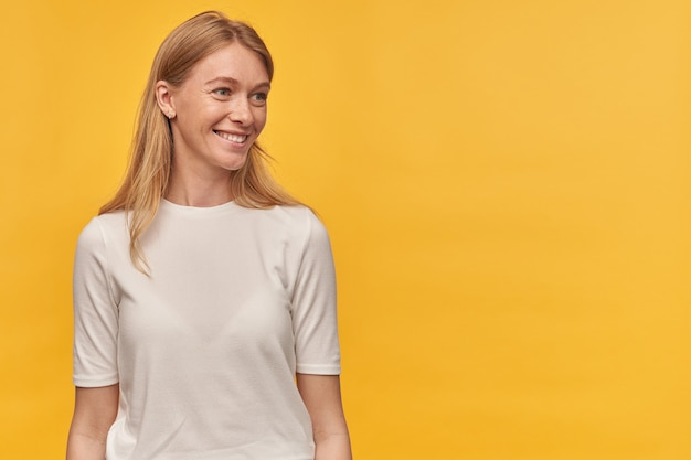 Cheerful attractive woman with freckles in white tshirt smiling and looking away to the side at empty space on yellow