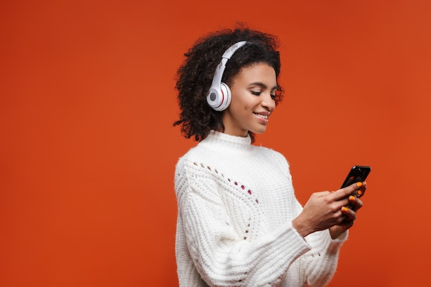 Cheerful attractive young african woman wearing wireless headphones standing isolated over red wall, using mobile phone