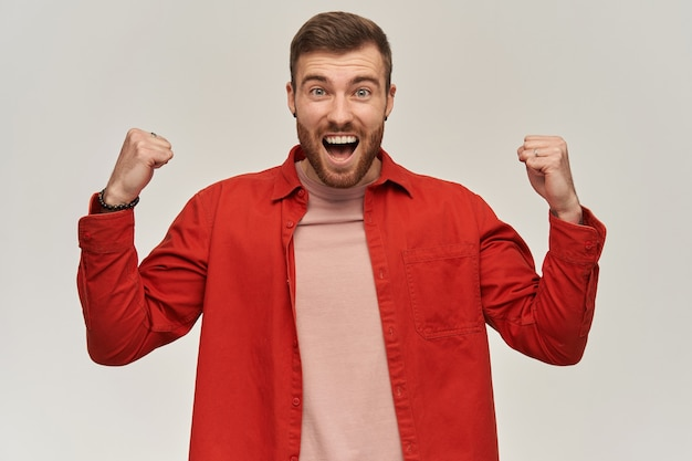 Cheerful attractive young bearded man in red shirt looks excited and celebrating victory over white wall