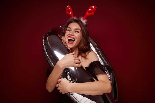 Cheerful attractive young brown haired woman with evening makeup standing into number air balloon and laughing happily, wearing christmas horns while posing