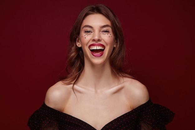 Allegro attraente giovane donna bruna con trucco festoso vestita in elegante top ridendo felicemente con un ampio sorriso mentre in piedi su sfondo bordeaux, essendo di alto spirito