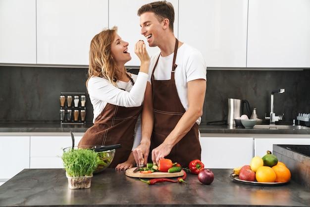 Веселая привлекательная молодая пара в фартуках стоит за кухонным столом, готовит свежий полезный салат, кормя друг друга
