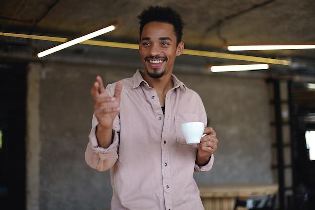 彼のオフィスのモダンな会議室に立って、会議の準備をし、コーヒーを飲み、同僚と楽しい時間を過ごす、短い巻き毛の陽気な魅力的な若い暗い肌のビジネスマン