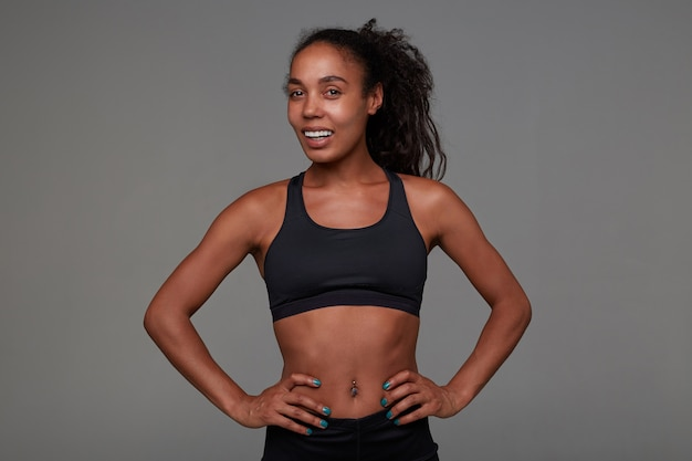 Cheerful attractive young dark skinned curly brunette lady in sporty black top looking positively with sincere smile, posing with hands on her waist