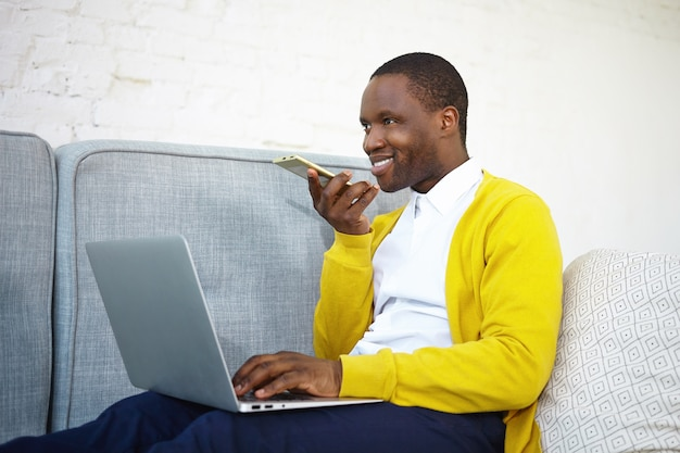 Cheerful attractive young dark skinned self employed male sitting on sofa with generic portable computer on his lap, working distantly from home, leaving voice message via cell phone and smiling