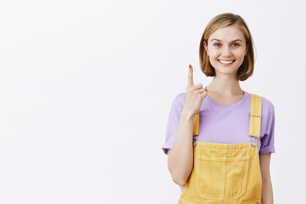Веселая привлекательная молодая девушка указывая пальцем вверх, показывая номер один