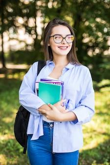 Giovane ragazza attraente allegra con i libri in piedi e sorridente nel parco
