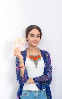 Cheerful attractive young lady holding singapore dollar cash