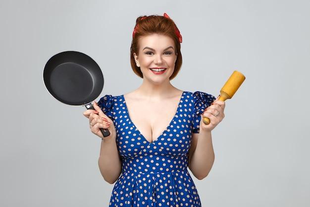 レトロな髪型とローカットのドレスを着て、片手に木製の乳棒を持ち、もう片方の手にフライパンを持って、新しい調理器具を自慢し、カメラに向かって幸せそうに笑っている陽気な魅力的な若い女性