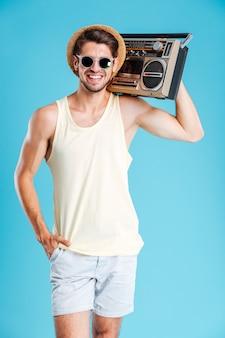 Веселый привлекательный молодой человек в шляпе и солнцезащитных очках стоит и держит бумбокс над синей стеной