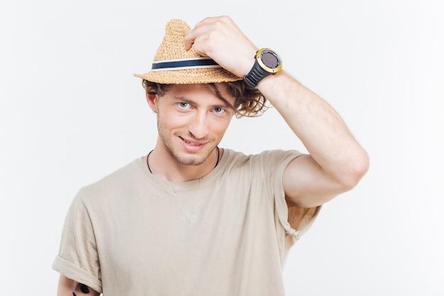 白い背景の上のカメラを見て帽子の陽気な魅力的な若い男