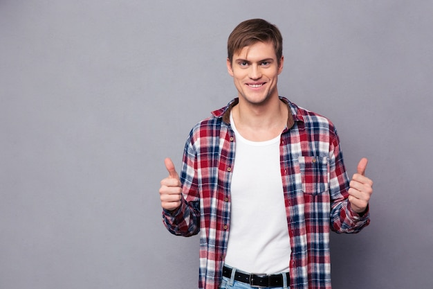 Cheerful attractive young man in plaid shirt showing thumbs up over grey wall