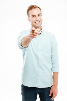Веселый привлекательный молодой человек улыбается и указывает на переднюю часть над белой стеной