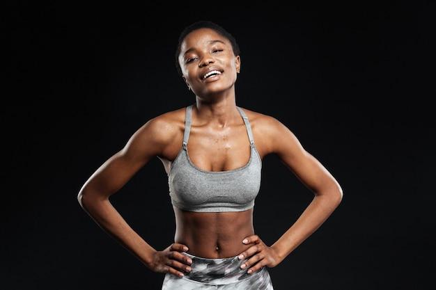 Веселая привлекательная молодая спортсменка позирует со сложенными руками над белой стеной Premium Фотографии