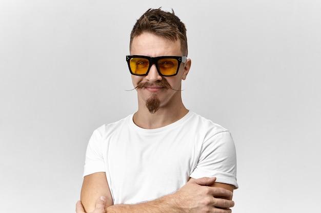 Веселый привлекательный молодой небритый мужчина со стильной прической, козлиной бородой и усами на руле в хорошем настроении, скрестив руки на груди и уверенно улыбается, в модных очках