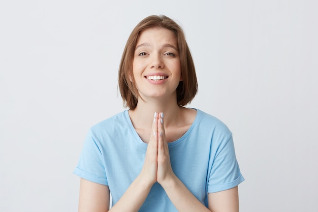 Cheerful attractive young woman in blue t shirt keeps hands folded in praying position