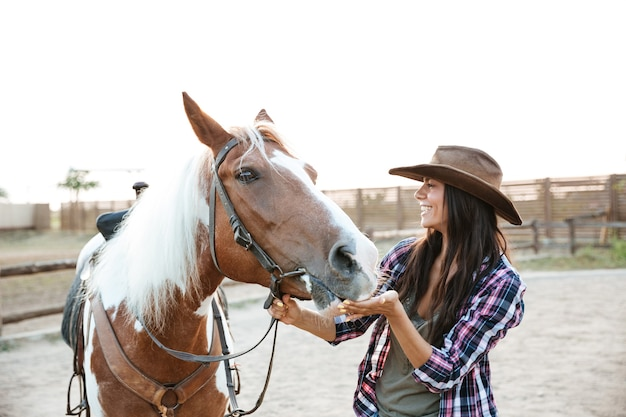 Cheerful attractive young woman cowgirl playing with horse in countryside