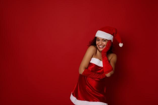 산타 카니발 의상을 입은 쾌활한 매력적인 젊은 여성은 아름다운 이빨 미소로 웃고, 카메라를 보고 기뻐하며 크리스마스와 새해 광고를 위한 복사 공간이 있는 빨간색 배경에 포즈를 취합니다.